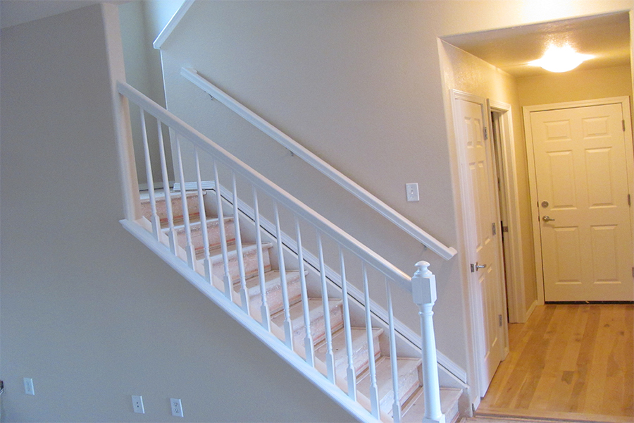 Interior painting beige walls with white accent colors on stair rails and doors.