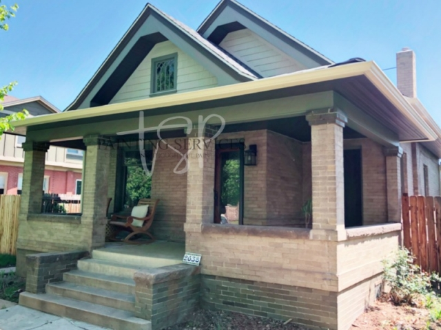 Exterior painting of a brick home with A-line roof